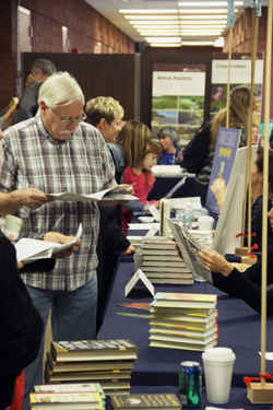 BBF attendees using their brochures to learn more about the books and authors.