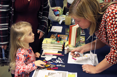Author Jennifer Maschari interacting with a book fair attendee.